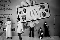 United Arab Emirates (UAE). Abu Dhabi. Underground access corridor to Sheikh Zayed Grand Mosque, the largest mosque in the country. A group of tourists stands by a future Mac Donald fast food. An advertising with an hand holding a menu card with Mac Donald logo, drawings of various hamburgers ( Double Royal Deluxe, Big Mac), a large pack of french fries and gifts for customers. Two Asian men wear a mask on their face to protect themselves from the Coronavirus disease (also called Covid-19). An App can be dowloaded from the Mac App Store. A man wears a thawb (thobe, dishdasha, kandora) which is an ankle-length garment, usually with long sleeves, similar to a robe, kaftan or tunic. It is commonly worn in the Arabian Peninsula. A sirwal or pants, izaar or lungi are typically worn underneath. The United Arab Emirates (UAE) is a country in Western Asia at the northeast end of the Arabian Peninsula. 20.02.2020  © 2020 Didier Ruef