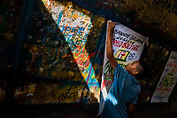 "A Colombian sign painter apprentice takes down a just-finished music party poster in the sign painting workshop in Cartagena, Colombia, 12 December 2017. Hidden in the dark, narrow alleys of Bazurto market, a group of dozen young men gathered around José Corredor (""Runner""), the master painter, produce every day hundreds of hand-painted posters. Although the vast majority of the production is designed for a cheap visual promotion of popular Champeta music parties, held every weekend around the city, Runner and his apprentices also create other graphic design artworks, based on brush lettering technique. Using simple brushes and bright paints, the artisanal workshop keeps the traditional sign painting art alive."