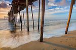Cape Hatteras National Seashore, Avon, North Carolina<br /> Sunrise reflections on surf and waves beneath the Avon fishing pier