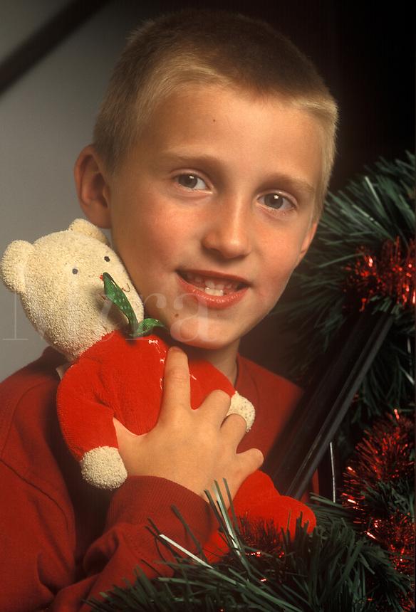 Boy holds Teddy Bear during Christmas holiday