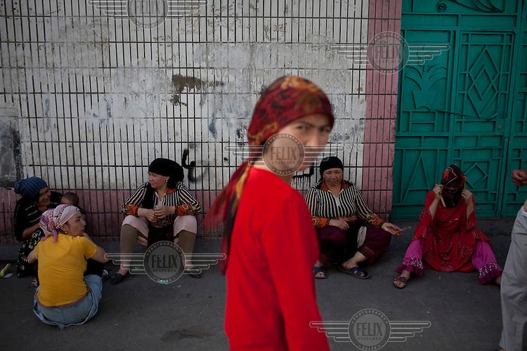 Women sit around in a Uighur neighbourhood in Urumqi.
