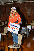 A woman stands on a chair holding a Make America Great Again sign as she watches Eric Trump, son of US president Donald Trump, greets people and signs MAGA hats and Trump campaign signs after speaking during a Make America Great Again! campaign rally at the DoubleTree by Hilton Manchester Downtown in Manchester, New Hampshire, on Mon., Oct. 19, 2020.