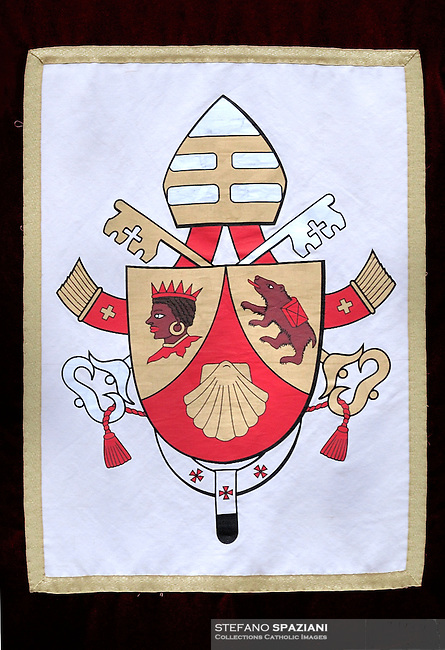 """The coat of arms of Pope Benedict XVI.The coat of arms of Pope Benedict XVI was designed by then Archbishop Andrea Cordero Lanza di Montezemolo (who later was created a Cardinal) soon after the papal election. Benedict's coat of arms has omitted the papal tiara, which traditionally appears in the background to designate the Pope's position as a worldly ruler like a king, replacing it with a simple mitre, emphasising his spiritual authority.[142]  . .Escutcheon Gules, chape in or, with the scallop shell of the second; the dexter chape with a moor's head in natural colour, crowned and collared of the first, the sinister chape a bear trippant in natural colour, carrying a pack gules belted sable . .Symbolism Scallop shell: The symbolism of the scallop shell is multiple, one of the meanings is thought to represent Saint Augustine. While a doctoral candidate in 1953, Fr. Joseph Ratzinger wrote his dissertation on The People of God and the House of God in Augustine's Teaching is always about the Church, and therefore has a personal connection with the thought of this great Doctor of the Church..Moor of Freising: The Moor's head is an heraldic charge associated with Freising, Germany..Corbinian's bear: A legend states that while travelling to Rome, Saint Corbinian's pack horse was killed by a bear. He commanded the bear to carry the load. Once he arrived, he released it from his service, and it returned to Bavaria. The implication is that """"Christianity tamed and domesticated the ferocity of paganism and thus laid the foundations for a great civilisation in the Duchy of Bavaria."""" At the same time, Corbinian's bear, as God's beast of burden, symbolises the weight of office that Benedict now carries. ."""