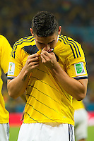 James Rodriguez of Columbia celebrates scoring a goal by kissing his shirt after making it 2-0