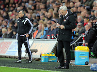 Crystal Palace manager Alan Pardew makes a note on the touchline (R) during the Barclays Premier League match between Swansea City and Crystal Palace at the Liberty Stadium, Swansea on February 06 2016