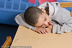 Educaton preschool 4-5 year olds boy sitting alone resting head on table sucking finger horizontal sad or tired