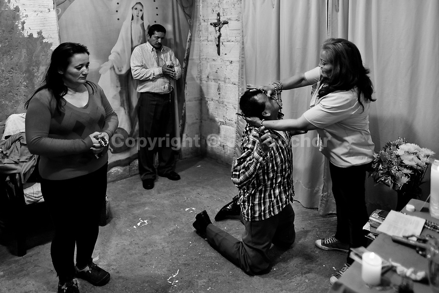 A Colombian pastor, pressing on a believer's head, attempts to evict a supposed demon during the exorcism ritual performed at a house church in Bogota, Colombia, 10 March 2016. Hundreds of Christian belivers, joined in nameless groups, gather every week in unmarked home churches dispersed in the city outskirts, to carry out prayers of liberation and exorcism. Community members and their religious activities are usually conducted by a charismatic pastor or preacher. Using either non-contactive methods (reading religous formulas from bible, displaying Christian symbols and icons) or rough body-pressure-points techniques and forced burping, a leading pastor commands the supposed evil spirit, which is generally believed to come from witchcraft, to depart a person's mind and body. The demon's expulsion often consists of multiple rites and may last for several months.