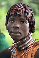 Ethiopia. Southern Nations, Nationalities, and Peoples' Region. Omo Valley. Turmi. Hamar tribe (also spelled Hamer). Pastoralist group. Woman's portrait. Hamar women wear an elaborately decorated goatskin, often colored with beads and cowries. Beaded necklaces, bracelets and waistbands adorn their bodies. They also wear thick copper necklaces announcing their marital status; a lather long tipped necklace and two copper necklaces if they are the first wife and only two copper necklaces if they are second, third, fourth wife to one man. Hamer women indulge in elaborate hairdressing by decorating their hair with clay and butter twisted into a striking long plait. The Omo Valley, situated in Africa's Great Rift Valley, is home to an estimated 200,000 indigenous peoples who have lived there for millennia. Amongst them are 60'000 to 70'000 Hamar, an Omotic community inhabiting southwestern Ethiopia. They live in Hamer woreda (or district), a fertile part of the Omo River valley, in the Debub Omo Zone of the Southern Nations, Nationalities, and Peoples Region (often abbreviated as SNNPR) which is one of the nine ethnic divisions of Ethiopia. 9.11.15 © 2015 Didier Ruef