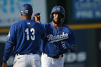 Luis Yanel Diaz (10) of the Rancho Cucamonga greets third base coach Johan Garcia after hitting a home run during a game against the San Jose Giants at LoanMart Field on August 22, 2021 in Rancho Cucamonga, California. (Larry Goren/Four Seam Images)