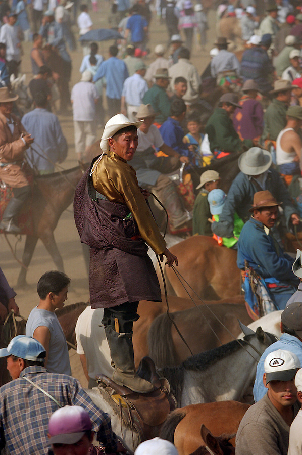 Khui Doloon Khudag, Mongolia, July 2003..Competitors & spectators at the horse racing in the national Naadam 40 kilometres outside Ulaanbaatar..A nomad stands on his horse to get a better view of the racing.