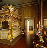 A regally ornate lit a la Polonaise dominates this bedroom at Osterley Park which features ruched fabric covered walls and a gilt chinoiserie console table