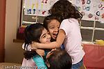 Preschool Headstart 3-5 year olds pretend play area group of girls in dressup hugging horizontal