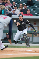 Charlotte Knights catcher Kevan Smith (32) flips the ball towards home plate as Daniel Fields (29) of the Toledo Mud Hens scores a run on the wild pitch in the top of the first inning at BB&T BallPark on April 27, 2015 in Charlotte, North Carolina.  The Knights defeated the Mud Hens 7-6 in 10 innings.   (Brian Westerholt/Four Seam Images)