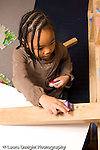 Education Preschool 4-5 year olds girl playing with toy cars and ramp she made out of wooden blocks vertical
