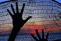Hands and fish net silhouette, Aurukun, Cape York Peninsula.