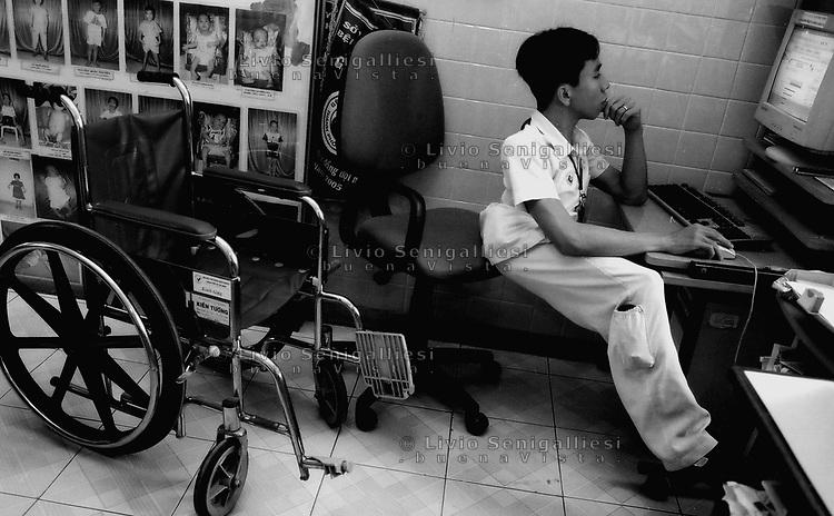 Tu Du Hospital - Ho Chi Minh City / Vietnam<br /> Conseguenze guerra in Vietnam 40 anni dopo.Nguyen Duc, 24 anni, vittima dell'agente arancio proviene dal villaggio di Sa Thay, una delle zone più contaminate dalla diossina. Pur affetto da gravi malformazioni conduce una vita quasi normale e lavora nello staff dell'ospedale. Il fratello Viet, a cui era unito alla nascita, è stato più sfortunato. Vegeta letteralmente nel letto, curato dalle infermiere e dalla madre Lam Thi di 52 anni, irrorata più volte durante la guerra dall'Agent Orange.Foto Livio Senigalliesi.<br /> Tu Du Hospital - Ho Chi Minh City / Vietnam<br /> Consequenses of the war in Vietnam 40 years later.Hospital for victims of Agent Orange / Dioxine Syndrome.In the picture Nguyen Duc born togher with his son Viet 24 years ago. The 2 twins came from the district of Sa Thay, in the Province of Kontum, one of the places most contaminated by the deadly herbicide.Joined at the pelvis, 2 legs, one penis, they were operated and divided when they were 8. Duc was luckier, thanks to the treatments he overcame the physical disabilities, studied and now is working in the staff of the hospital. His brother Viet has been vegetating in his bed, attended by the nurses and by his mother La Thi (52) sprayed during the war times by US airplanes.<br /> Photo Livio Senigalliesi