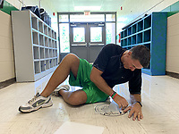 Alan Barton, longtime Greenland Elementary School principal, applies decals to the floor to help students with social distancing Thursday, Aug. 6, 2020, as he and his staff prepare the school to meet social-distancing and other covid-19 standards ahead of the first day of school. Visit nwaonline.com/200807Daily/ for today's photo gallery.<br /> (NWA Democrat-Gazette/Andy Shupe)