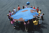 "MR / Schenectady, NY. Yates Arts in Education Magnet Elementary School. Grade 3 inclusion classroom. Students (including some special education students) play ""earth ball"" game which requires them to work together to bounce ball. The students painted this canvas circle in art class so this was an integrated curriculum project including social studies, art and physical education lessons. MR: AJ-LC. ID: AJ-LC. © Ellen B. Senisi"
