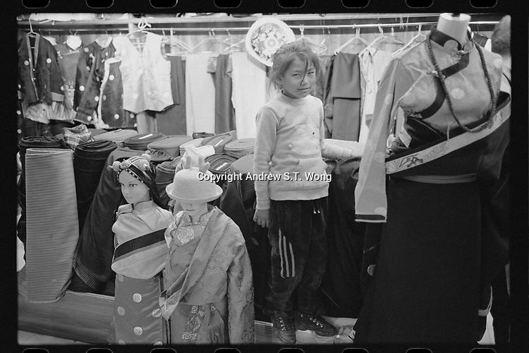Nangqen County, Yushu Tibetan Autonomous Prefecture, Qinghai Province, China - A Tibetan girl helps mother sell traditional costumes at a shop, August 2019.