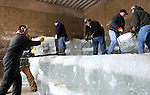 Volunteers stack the blocks of ice, harvested from a local pond, into an insulated storage building until needed for summertime events.