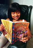 Lilia, age 8, reads the first of the Harry Potter books - Harry Potter and the Sorcerer's Stone. Lilia Santa Maria. Culver City, California.
