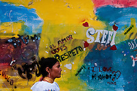 """A woman passes in front of a colorfully paited wall during the Inti Raymi fiesta in Pichincha province, Ecuador, 26 June 2010. Inti Raymi, """"Festival of the Sun"""" in Quechua language, is an ancient spiritual ceremony held in the Indian regions of the Andes, mainly in Ecuador and Peru. The lively celebration, set by the winter solstice, goes on for various days. The highland Indians, wearing beautiful costumes, dance, drink and sing with no rest. Colorful processions in honor of the God Inti (Sun) pass through the mountain villages giving thanks for the harvest and expressing their deep relation to the Mother Earth (Pachamama)."""