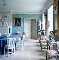 A pair of giltwood mirrors hangs on the walls  of the dining room with a pair of marble busts in the window bays