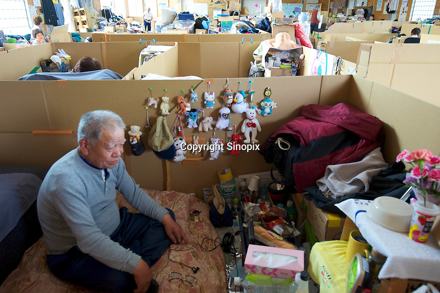 Mr Sugawara, sitting in a cardboard box within a Government shelter, that he shares with his wife,  in Minamisanriku, Myiagi, Japan. The fishing port of Minamisanriku, Miyagi, Japan was devastated by the tsunami where the popultion was reduced from 18,000 to about 8,000 when 10,0000 where washed out to sea.<br /> <br /> Photo by Richard Jones/ Sinopix