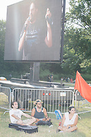 People sit in the shade listening to a speaker from Occupy Monsanto (on the screen) in the protest area in FDR Park outside of the secure area surrounding the Democratic National Convention at the Wells Fargo Center in Philadelphia, Pennsylvania, on Wed., July 27, 2016.