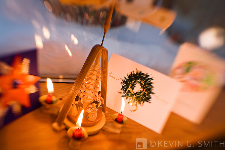 Close up of a window sill decorated for christmas, candle powered wooden carousel in foreground, snow outside in background, selective focus.