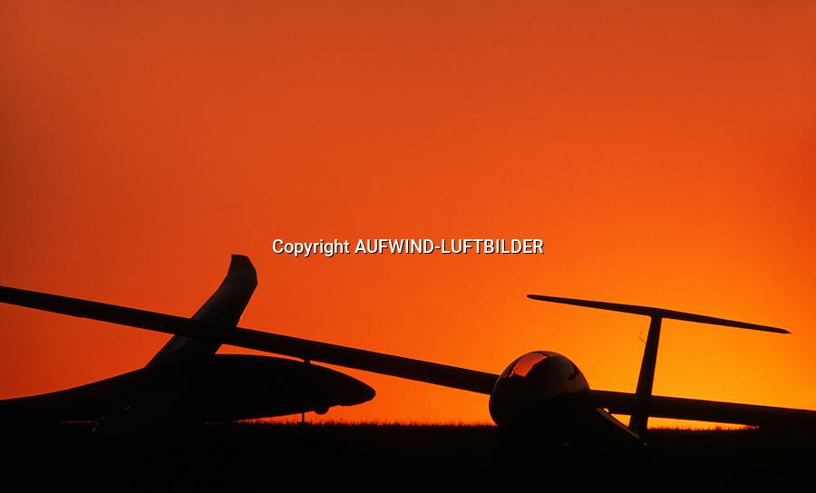 Segelflugzeuge im Abendlicht: DEUTSCHLAND, HAMBURG 23.09.2014: Nach einem Flugtag stehen zwei doppelsitzige Segelflugzeuge vom Typ Duo Diskus und DG 100 im roten Abendlicht.