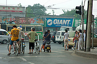People on bicycles stopped at a red traffic light, Hutong district, Beijing, China.