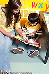 Education preschool female volunteer intern reading picture book to boy 3 year olds vertical