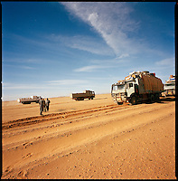 Sahara desert, Libya-Chad, November/December 2004..Every week, a convoy of 40 privately owned Libyan trucks loaded by the WFP with about 1000 metric tons of western food aid cross 2500 km of deep desert across Libya and Chad to reach more than 200 000 refugees from Darfur in camps near the Sudanese border. A rare encounter in the middle of the desert: empty trucks from a preceding convoy give informations on the way yet to cover...