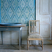 Detail of blue and white French Directoire wallpaper and a chair against the wall in the dining room