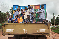 Nigeria. Enugu State. On the road to Enugu. A truck carries plastic crates with lager beer bottles and schoolchildren on their way back from school. One of the boys holds in his hands a bottle of Life Continental Lager beer which is the fine quality lager beer from the stables of Nigerian Breweries Plc made from the choicest grains, hops and the purest of waters. Igbo students, all boys, laughing and pulling faces while standing on lorry's trailer. Some pupils blue and white uniforms. 5.07.19 © 2019 Didier Ruef