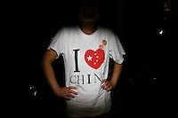 CHINA. Beijing. A woman wearing an 'I Love China' t-shirt whilst watching the opening ceremony of the Beijing Summer Olympics. 2008