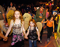 Sisters Hellaina Wortnan (CQed) (left), 10, and Zarria Dennis, 5, walk in the Parade of Little Angels Saturday night. The event was part of All Souls Procession festivities and took place at the downtown main library, 100 North Stone Ave.