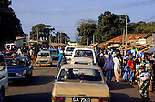 Banjul, Gambia. Busy street with market stalls and traffic.