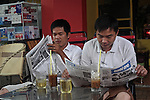Two men read the paper and drink iced coffee one early morning in Pham Ngu Lao Ward, Ho Chi Minh City, Vietnam. Aug. 27, 2011.