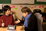 Education elementary grade 4  female teacher discussing behavior issues with male student sitting at desk horizontal