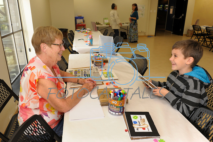 Volunteer Judi Miller, left,  and Nicolau Philibert, 7, talk about the flower press the child made during Nevada Wildflower Family Fun Day at the Nevada State Museum in Carson City Saturday April 11, 2015. Visitors to the museum were treated to loads of information, hands-on experiences and crafts.<br />