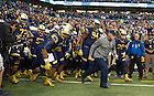 Sept 13, 2014; Coach Brian Kelly runs out on the field with his team before kickoff  against Purdue in the Shamrock Series football game in Indianapolis. (Photo by Barbara Johnston/University of Notre Dame)