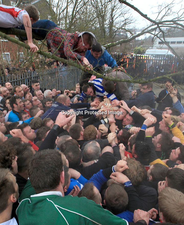 12/02/13 ..Players reach for the ball in the annual Royal Shrovetide Football match in Ashbourne, Derbyshire. ..Shrovetide Football is played every Shrove Tuesday and Ash Wednesday. Unlike a conventional football match this game is played over two eight hour periods, the goals are three miles apart and there are very few rules...The leather ball which has a cork inner is 'turned up' from a stone plinth on Shaw Croft car park in Ashbourne town centre. The ball is thrown into the air and into the 'hug', a large group of players who try to move the ball to their goal by pushing against the opposition...Your team depends on which side of the Henmore brooke you were born on, those born on the South are Down'ards and try to goal the ball at the old Clifton Mill. Those born on the North are Up'ards and try to goal the ball at the old Sturston Mill...All Rights Reserved - F Stop Press.  www.fstoppress.com. Tel: +44 (0)1335 300098.
