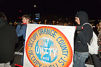 Marchers hold the Occupy Orange County sign while marching at South Coast Plaza early in the morning (1:17am)  on Black Friday.  A lit South Coast Plaza sign is lit in the background.   The protesters were tied together by rope, being led by a single protestor dressed in a suit (as a banker), symbolizing how the 1% lead the 99%.