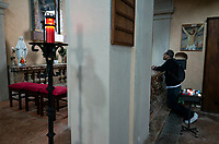 Switzerland. Canton Ticino. Brè. Catholic church. The photographer Joseph Rodriguez prays on his knees. The village of Brè lies on the eastern slope of Monte Brè. 23.03.2019 © 2019 Didier Ruef
