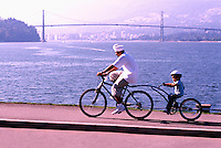 Stanley Park, Vancouver, BC, British Columbia, Canada - Father and Son cycling on Tandem Bikes on Seawall along Burrard Inlet in Summer - Lions Gate Bridge, West Vancouver, and North Shore Mountains in background