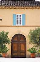 The main entrance and building. Wooden door, window with blue shutters. Chateau de Beaucastel, Domaines Perrin, Courthézon Courthezon Vaucluse France Europe