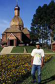 Curitiba, Parana State, Brazil. The Ukrainian Immigrants memorial; worker in Curitiba t-shirt.