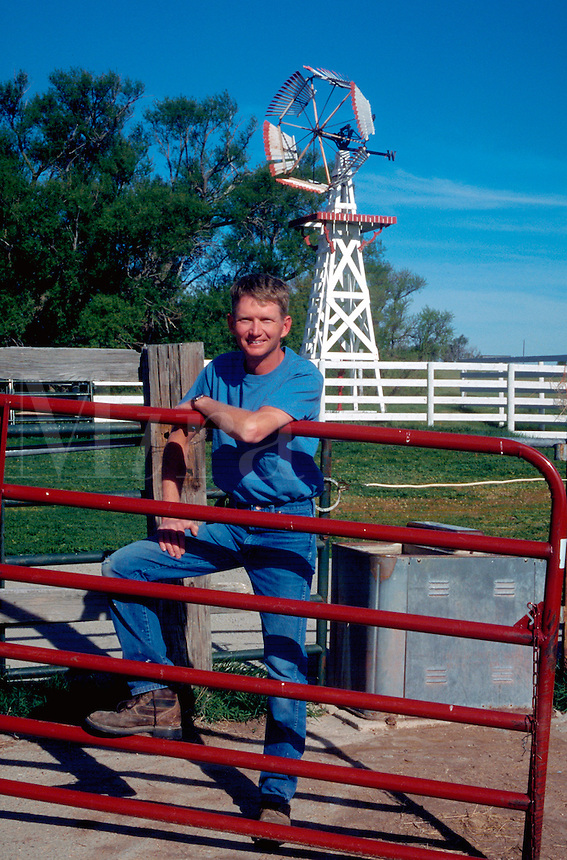 Portrait of a smiling farmer leaning on a gate.
